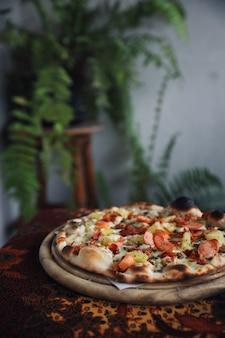 Pizza saucisse au bacon et à l'ananas sur bois, pizza hawaïenne