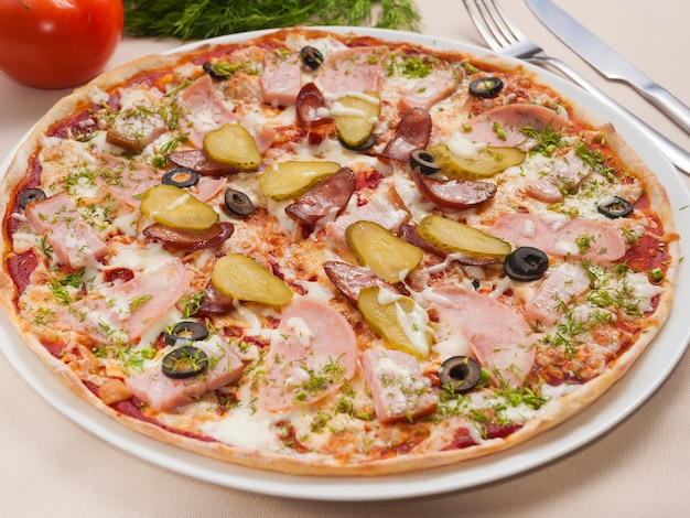 Pizza savoureuse avec des cornichons à la saucisse de viande et des olives