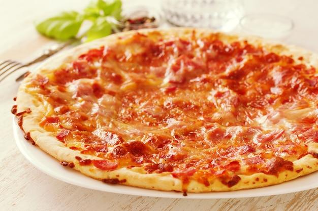Pizza sur une surface en bois blanche
