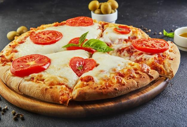 Pizza talian et ingrédients pour cuisiner sur un fond de béton noir. tomates, olives, basilic et épices. triangle de pizza en tranches.