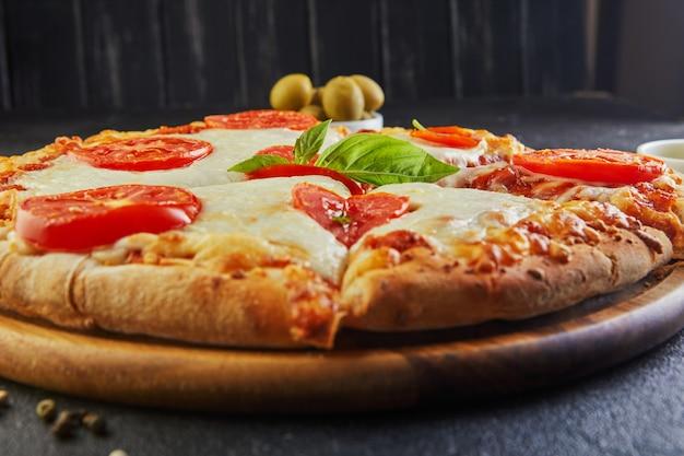 Pizza talian et ingrédients pour cuisiner sur un fond de béton noir