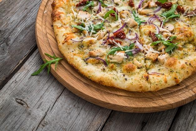 Pizza tomates séchées, prosciutto, roquette et parmesan