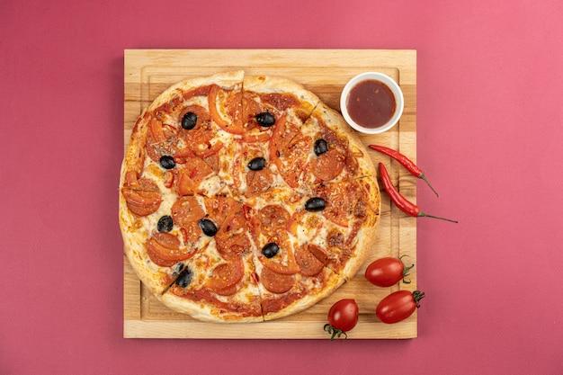 Pizza traditionnelle à la main sur table rouge