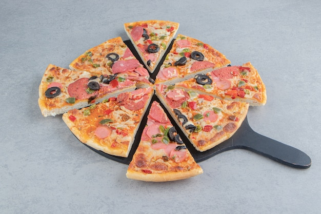 Pizza tranchée soigneusement sur une planche sur du marbre