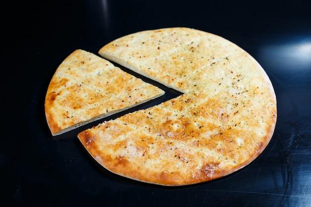 Pizza en tranches sur fond noir en pierre, vue de dessus. focaccia fraîchement cuite au fromage