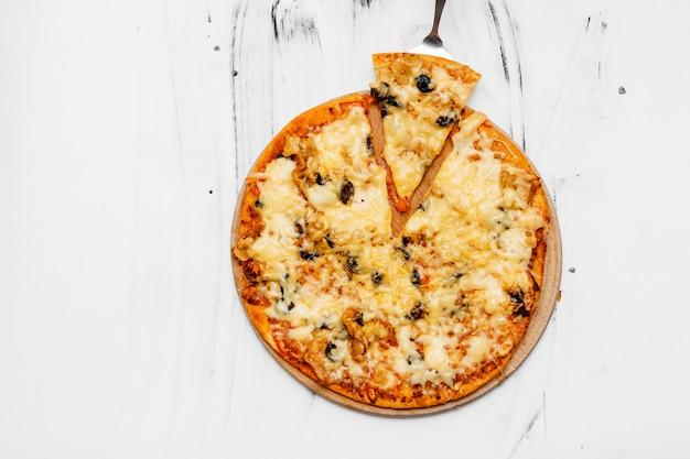 Pizza en tranches avec des ingrédients sur fond blanc. vue de dessus, mise à plat avec espace de copie.