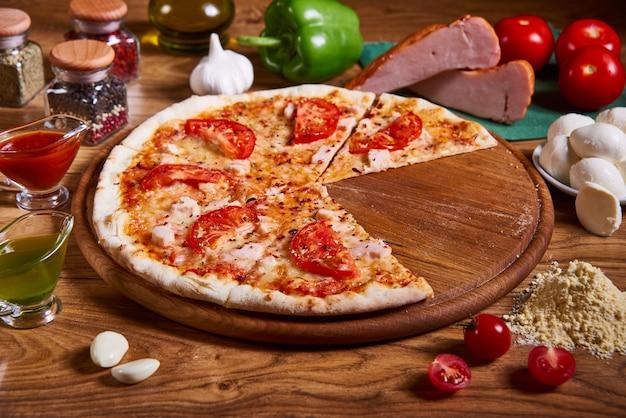 Pizza en tranches. pizza margarita à la sauce tomate, mozzarella fraîche, parmesan et basilic sur le bois rouillé