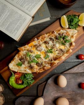 Pizza turque pide avec des aliments mélangés et des herbes.