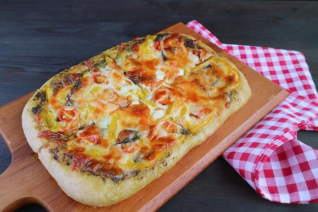 Pizza végétarienne au pesto maison fraîche et alléchante sur une planche à pain en bois