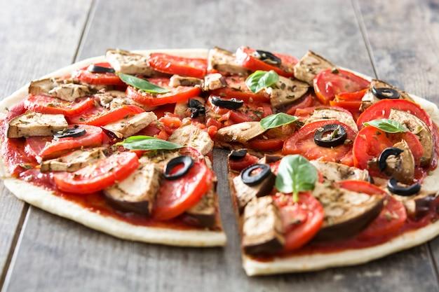 Pizza végétarienne aux aubergines, tomates, olives noires, origan et basilic sur table en bois