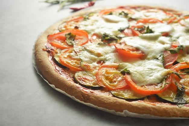 Pizza végétarienne à base de pâte de grains entiers, avec courgettes, tomates et mozzarella.