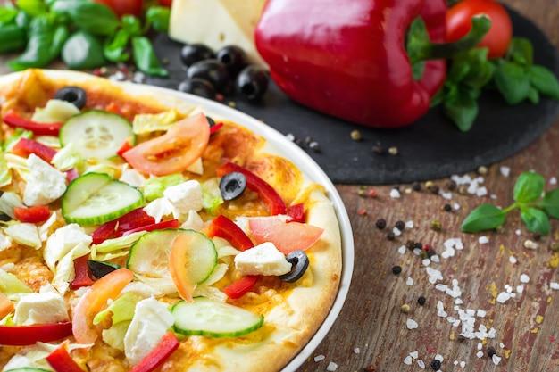 Pizza végétarienne avec des légumes et des ingrédients sur un fond en bois