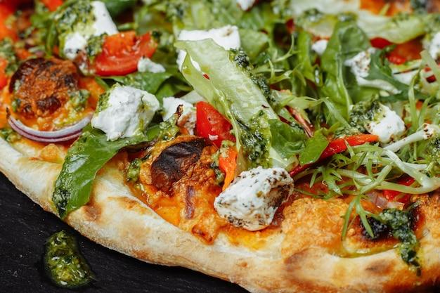 Pizza végétarienne avec tomates au fromage et légumes verts.