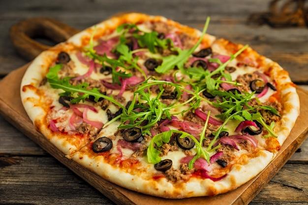 Pizza à la viande hachée, olives noires, oignon, roquette, fromage et sauce tomate, sur planche de bois