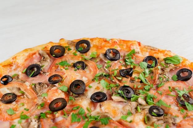 Pizza à la viande, olives, tomates, champignons, herbes isolés sur une surface en bois blanc