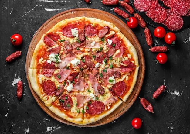 Pizza à la viande avec salami, jambon, poulet, saucisses et fromage feta, sur un tableau noir et sur une surface sombre