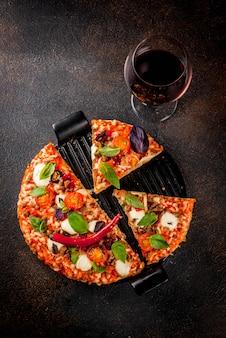 Pizza et vin rouge sur fond sombre