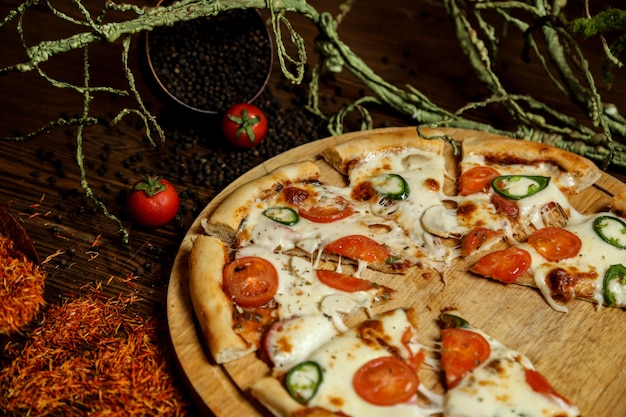Pizza vue de côté sur un stand avec tomates et poivre noir