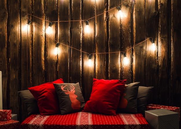 Place décorée de noël dans une chambre avec vieux mur en bois, lampes, oreillers de cerf rouge et plaid