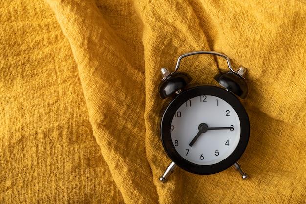 La place de l'horloge noire sur le tissu jaune