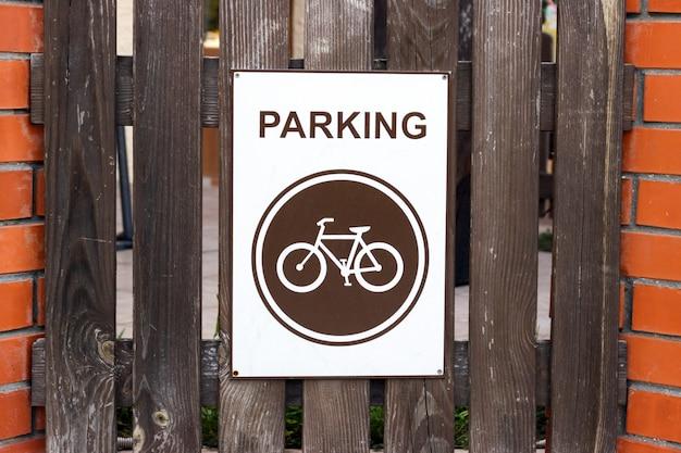 Une place de parking pour les vélos, un signe sur une clôture en bois