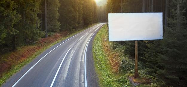 Place pour le texte ou la publicité. panneau d'affichage à côté d'une route de montagne.