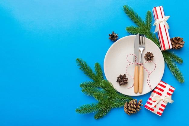Place de table de noël avec décor de noël et assiettes, kine, fourchette et cuillère. fond de vacances de noël. vue de dessus avec espace de copie