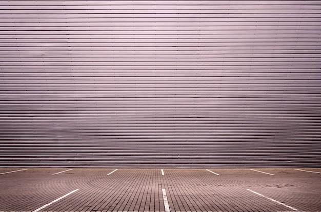 Places de stationnement vides sur le fond d'un mur en métal avec un espace pour le placement du produit