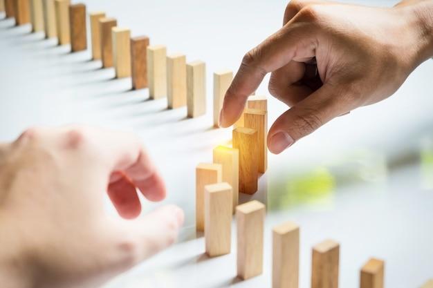 Placez une ligne de blocs en bois une équipe d'affaires résolvent un problème