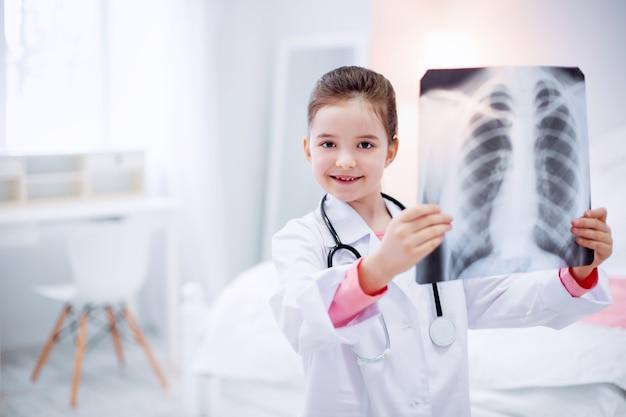 Placez sur la lumière. optimiste énergique petite fille radiographie en hausse en se tenant debout sur un arrière-plan flou et souriant