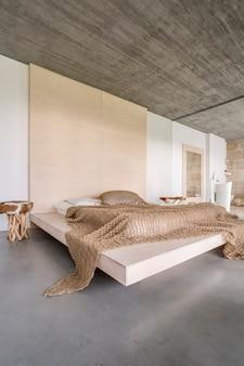 Plafond en bois dans une chambre spacieuse avec une grande tête de lit au-dessus du lit