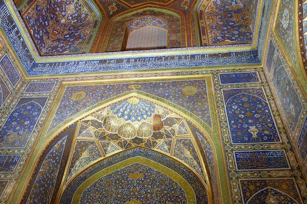 Plafond décoré d'or et de mosaïques à l'intérieur du sherdor madrasah, l'oulougbek sur la place du registan à samarkand. 29.04.2019