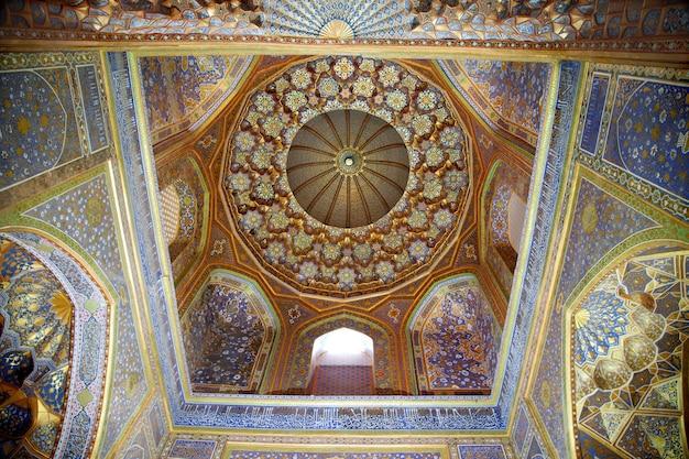 Plafond décoré d'or et de mosaïques à l'intérieur de la médersa d'oulougbek sur la place du registan à samarkand. 29.04.2019