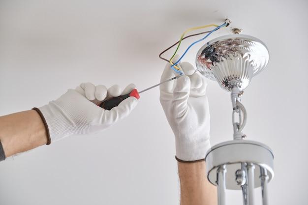 Plafonnier d'installation, mains d'électricien masculin fixant le lustre à l'aide d'outils professionnels