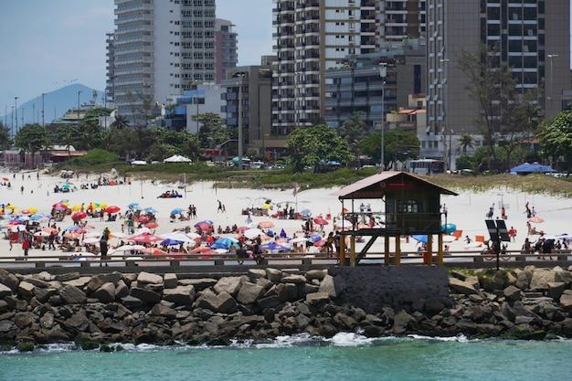 Plage de barra da tijuca par une journée ensoleillée avec des gens profitant du sable et de la mer. vue sur le brise-lames, le canal de barra et praia dos amores. rio de janeiro, rj, brésil. février 2021.