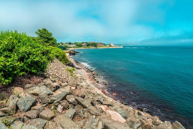 Plage bleue avec des rochers et des maisons sur la rive avec espace de copie pour le texte, plage bleue avec espace copie pour la publicité touristique