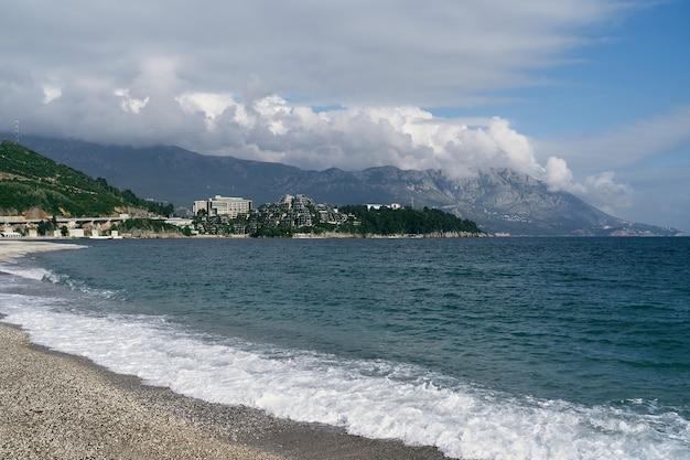 Plage à budva avec vue sur la mer, les montagnes et les bâtiments