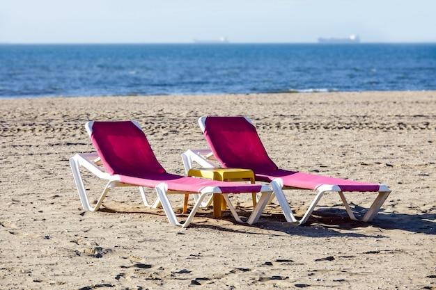 Plage chaise longue mer sable ciel horizon signes publicité noir bleu rose rouge