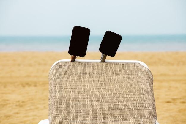 Plage chaise longue mer sable ciel horizon signes publicité noir bleu