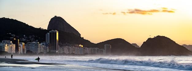 Plage de copacabana à rio de janeiro avec le mont du pain de sucre au coucher du soleil