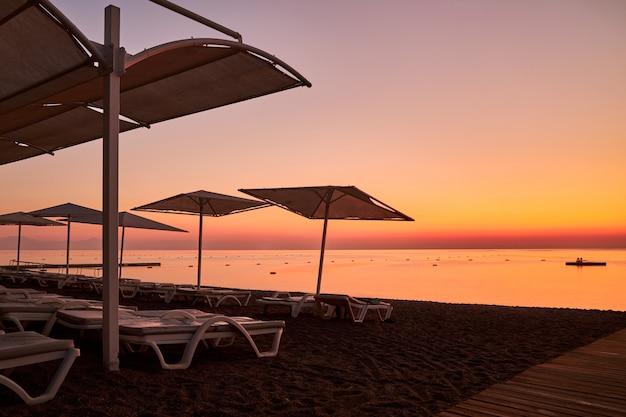 Plage déserte équipée de parasols et de chaises longues avant l'aube