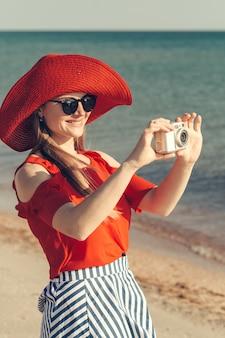 Plage d'été femme tenant une caméra prenant une photo