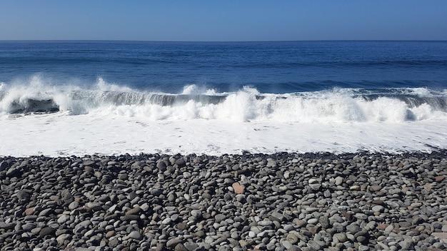 Plage de galets avec vagues de l'océan, personne, liberté et tranquillité sous un ciel bleu