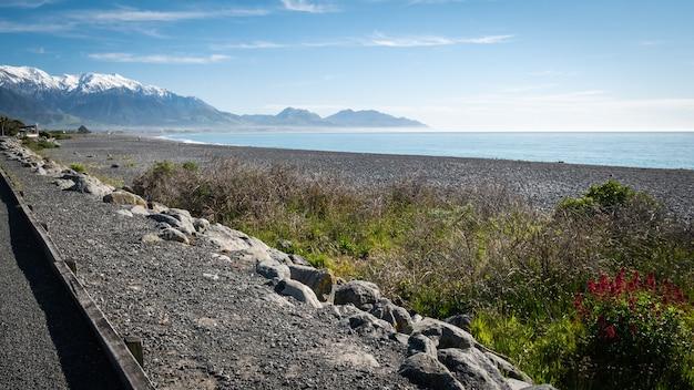 Plage isolée aux eaux azur, ciel bleu et montagnes en toile de fond kaikouranew zealand