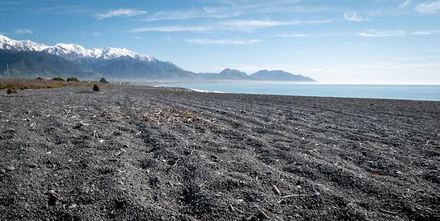 Plage isolée avec des eaux azurées de gravier noir, un ciel bleu et des montagnes kaikouranew zealand