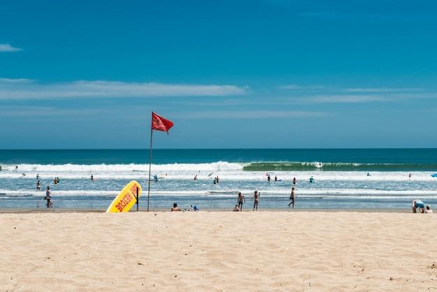 Plage de kuta, bali, indonésie. point de sauvetage de surf. planche de surf de sauvetage jaune et drapeau rouge.