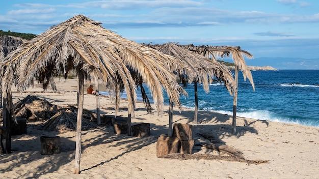 Plage de la mer égée avec des parasols en branches de palmier en grèce