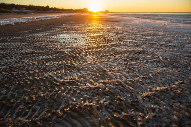 Plage de mer gelée sur le sinset. vagues de sable couvertes de glace.