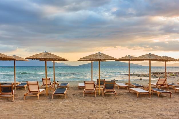 Plage de la mer avec des rangées de parasols en paille au coucher du soleil, île d'egine, grèce - paysage grec