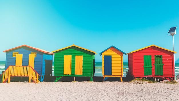 Plage de muizenberg avec sable blanc et cabanes en bois colorées à cape town, afrique du sud